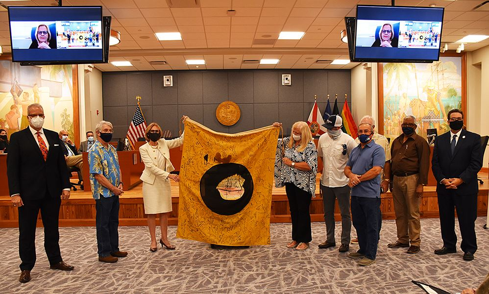 Photo of flag being presented to Commission.